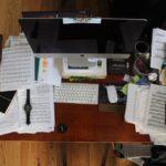 書類などが山積みにされたPCまわり