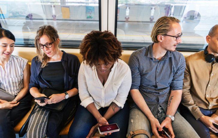 電車でスマホをみる人たち